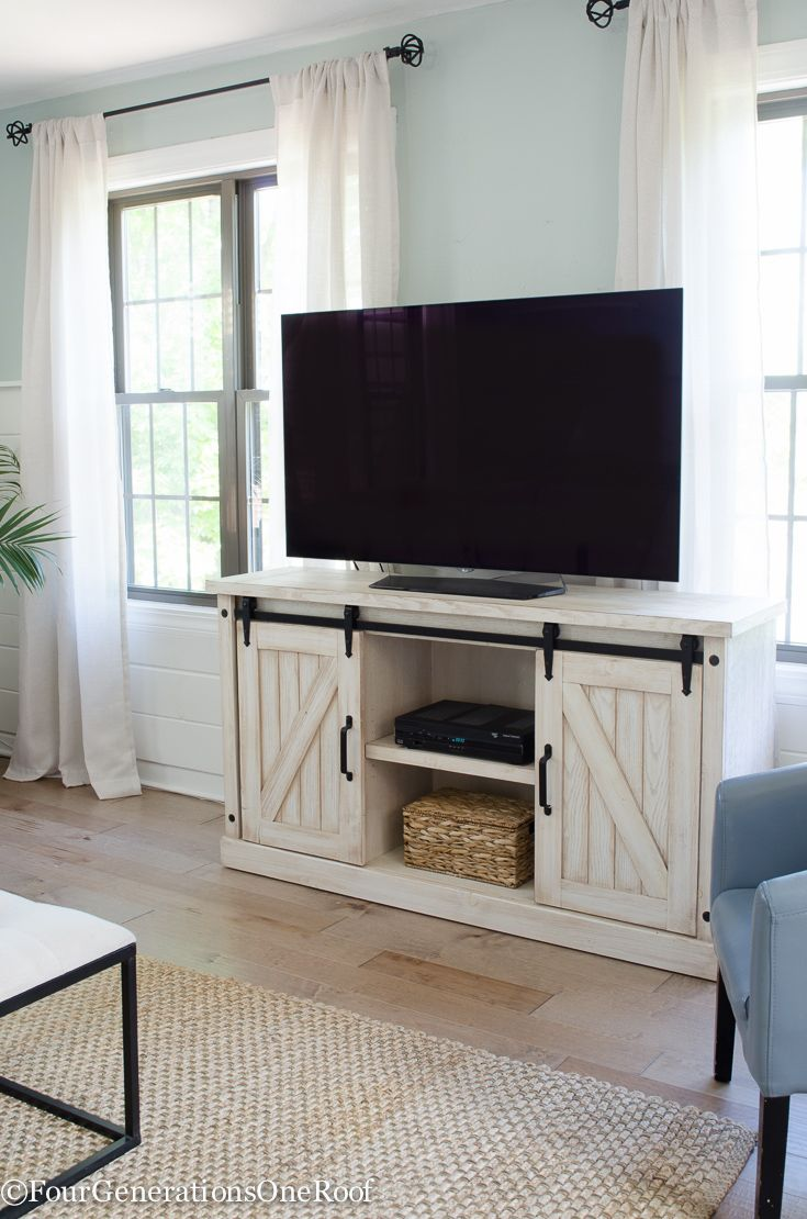 Hello gorgeous barn door sliding media console from HomeGoods! (sponsored). I love that the doors slide and all the media components are hidden! Coastal Transitional Living Room | Four Generations One Roof | Wall Paint Rainwashed Sherwin-Williams