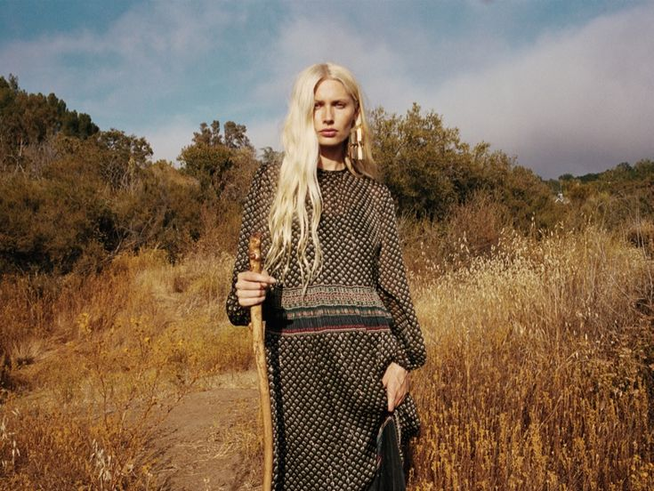 Kirsty Hume poses with a staff while wearing long sleeve dress