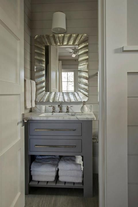 Modern cottage bathroom with gray batten walls and gray washed wood bathroom floors, ...