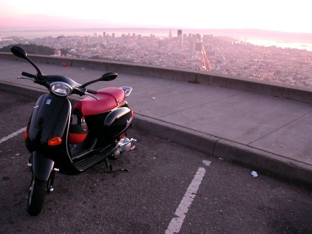 A beautiful black Vespa ET4 150cc with a red vinyl seat at Twin Peaks in San Fransisco. She belongs to a friend of mine.