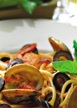 Spicy Olive and Seafood Spaghetti features shrimp, clams, and mussels in a tomato-white wine sauce perked up with red pepper flakes and minced garlic.