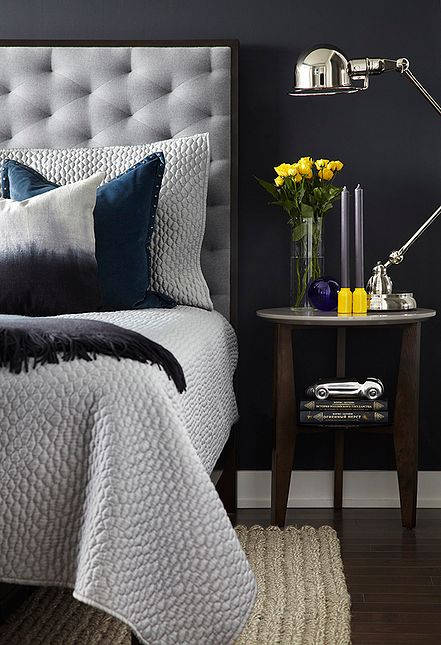 Master bedroom detail. Dark blue wall, king-size bed with a grey tufted wool headboard in a dark-chocolate wood frame (West Elm). Pharmacy table lamp in polished chrome (Restoration Hardware). Raw silk ombre pillow, blue gray quilt and shams, dark blue velvet pillow, extra soft mohair ombre throw. Hand-woven natural wool rug. Mid-century style side table (Structube). Yellow candleholders with gray candlesticks (CB2), yellow roses in a glass vase.