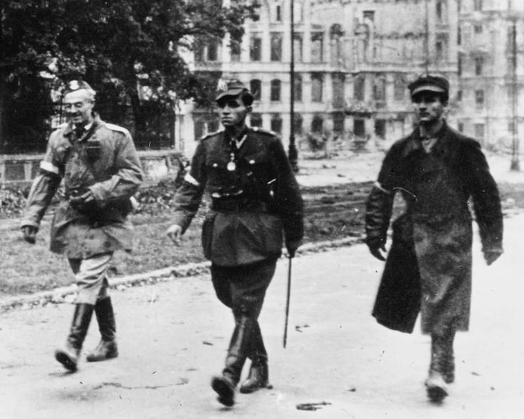"""Warsaw Uprising, Aug-Oct 1944: Polish officers, belonging to the national Polish liberation forces, make their way to German positions, after further resistance became untenable. Red Army forces remained outside the besieged city on Stalin's orders."""