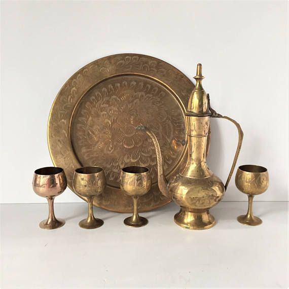 Vintage decorative tea or coffee set in a traditional etched brass style typical of Indian design, consisting of a ewer-shaped teapot or coffee pot, four cups or goblets and a round tray. The tray has an all-over floral design with central flower and measures 10 in. in diameter. The serving pitcher measures 8 5/8 in. tall. The cups measure 3 in. tall Very much in keeping with 1970s bohemian style harking to Turkish and Asian design, this set is in very good vintage condition, with lovely...