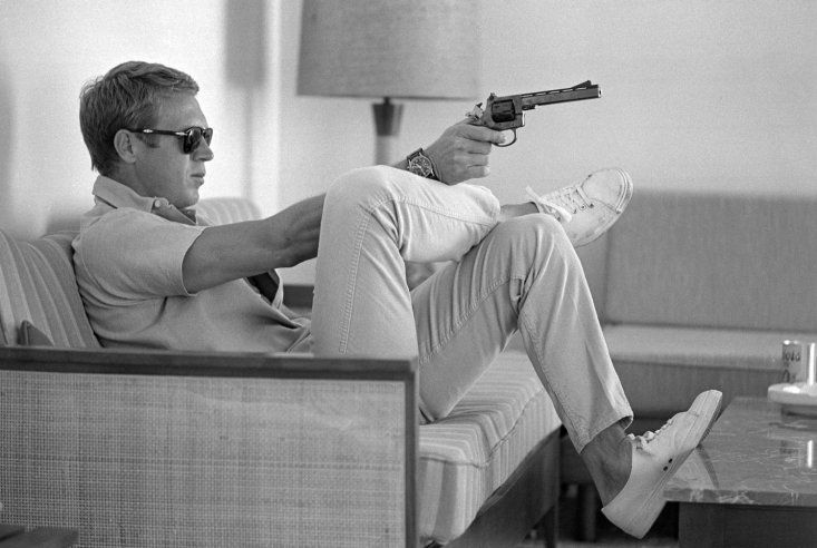 At his home in Palm Springs, Steve McQueen practices his aim before heading out for a shooting session in the desert