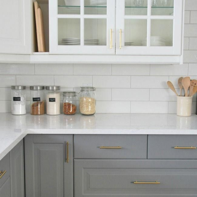 A Grey And White Kitchen Featuring A White Subway Tile Backsplash