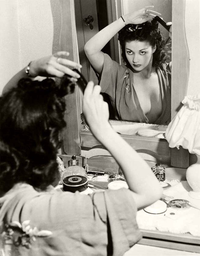 Yvonne De Carlo styling her hair, 1940s. Photo by Joseph Jasgur. #vintage #actresses #hair