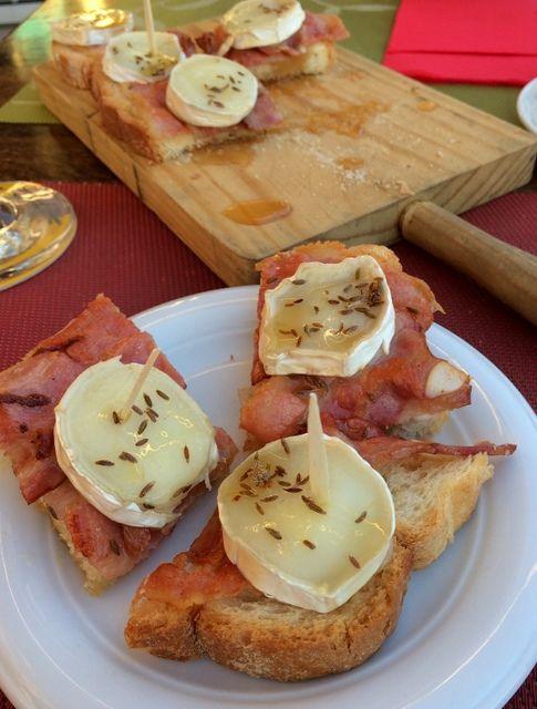 Het tapasplankje bestaat uit brood met krokante bacon, warme geitenkaas, honing en karwijzaad. Que aproveche!
