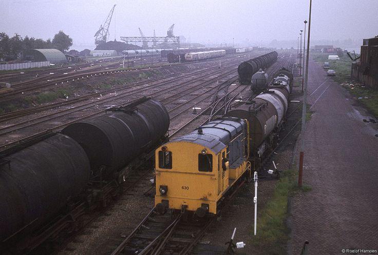 Een rangeerloc verplaatst een paar ketelwagens op Amsterdam Rietlanden, 5 juni 1979. Het spoor naar de noordelijke kade van het Spoorwegbassin (rechts) is duidelijk niet meer in gebruik. Links de erts- en kolenoverslag met helemaal achteraan de aanlegsteiger voor de spoorpont over het IJ naar het raccordement Dislelweg in Amsterdam Noord.