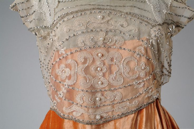 1921 Orange velvet evening gown. Orange velvet evening gown with a bodice of embroidered net with pearls, rhinestones and crystal beads. Low tunic effect skirt. Detail