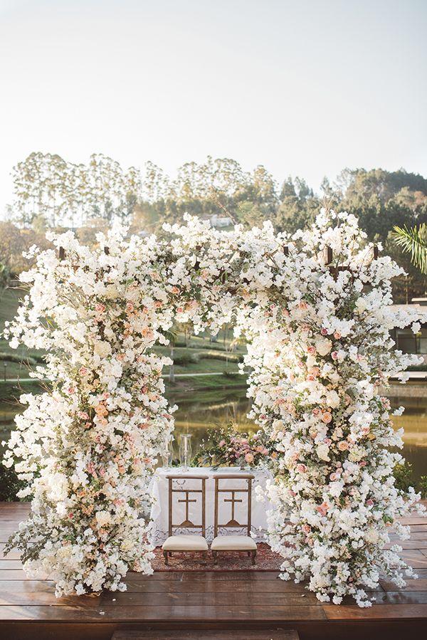 Altar coberto de flores em tons de branco e rosa - casamento romântico no campo - cerimônia à beira do lago ( Foto: Lucas Lima | Decoração: Fabio Borgatto e Telma Hayashi | Local: Terras de Clara )