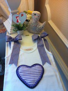 Camiseta blanca de sisas con corazón de rayas violeta y dos lazotes en los hombros.