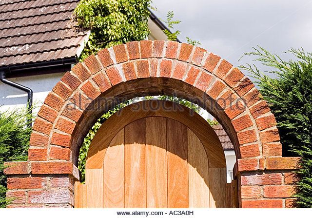 Curved red brick arch over garden gateway with wooden door Woodmancote UK - Stock Image