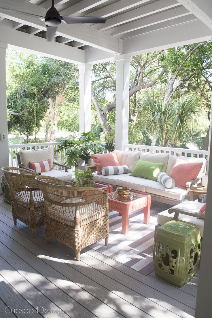 Outdoor patio sitting area with green and coral accents and whicker rattan furniture