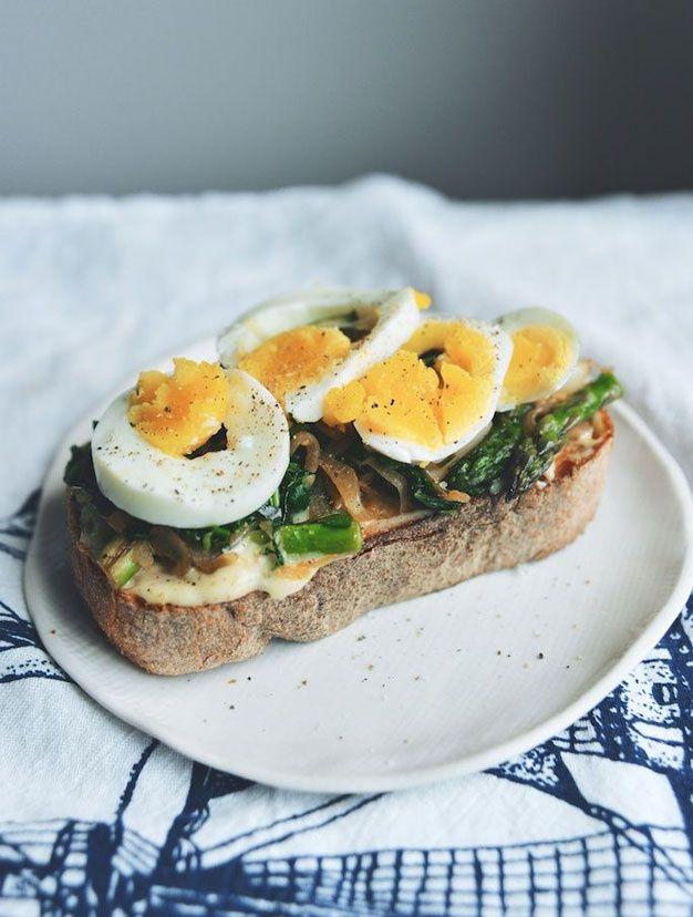 œufs durs au cœur fondant, des asperges et une sauce à l'oignon cébette sur une épaisse tranche de pain
