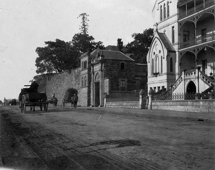 Horse drawn carts passing along Ann Street, Brisbane, 1914 - Photograph shows part of St Ann's Industrial School and the stone wall and entry to All Hallow's School along Ann Street