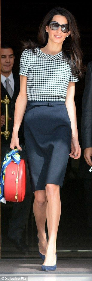Gingham girls: Amal Clooney arrived at London's Heathrow from Greece yesterday in a black-...