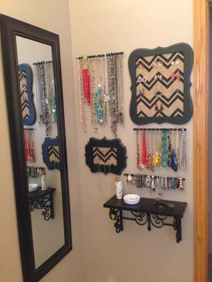cute and creative way to store and display your jewelry in your bathroom - small shelf, short rods, and black wooden plaques.