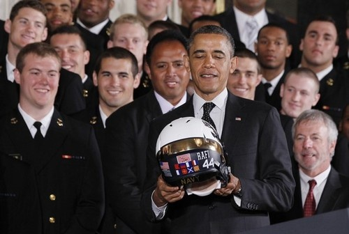 U.S. President Barack Obama looks down at the helmet presented to him by the U.S. Naval Academy football team after he honored them at a presentation ceremony for the Command