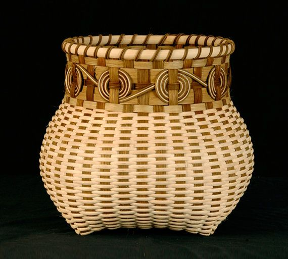 In this cats head shape basket I used natural and earthy tones. At the neck of the basket I weaved Cherokee wheels; a traditional design that can be