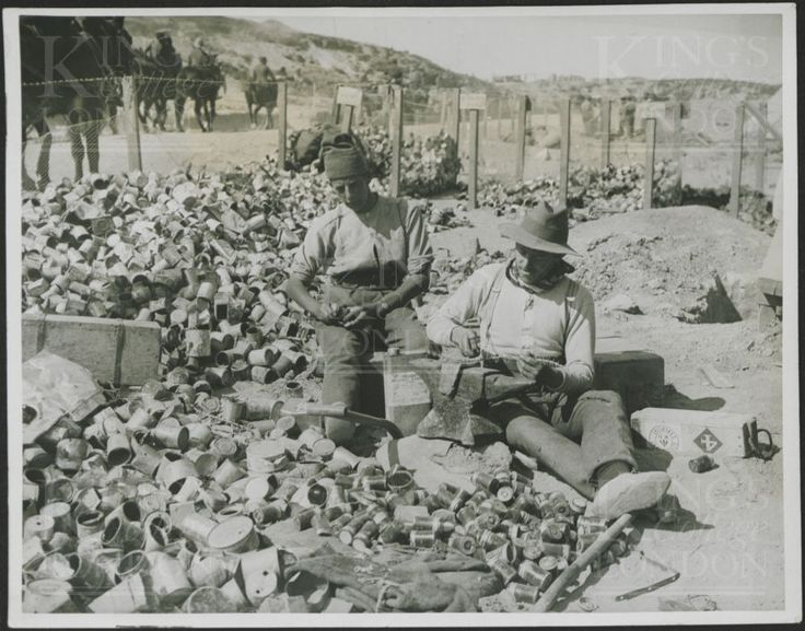 """Photograph of two British and ANZAC soldiers manufacturing 'jam tin' grenades. No 2612. The caption on the reverse reads """"Men at work making bombs. All the old jam tins and other similar receptacles are used in making bombs, even fragments of Turkish shells and enemy barbed wire are cut up and used as 'filling'."""" From a collection of official photographs of the Dardanelles Expedition, 1915-1916."""