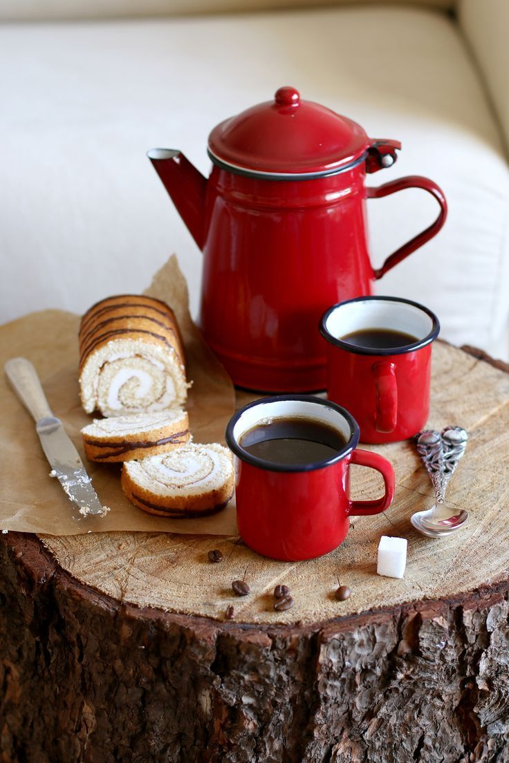 Enamel mugs with hot coffee and enamel kettle on a rustic wooden board