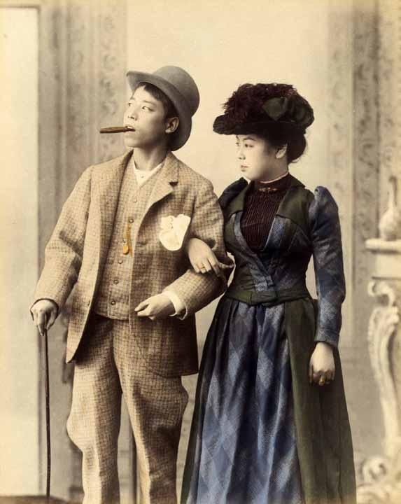 Portrait of a young Japanese couple in western clothes, circa 1890 by Kusakabe Kimbei , Japan  1841-1934. Albumen silver photograph, colour dyes, image 24.0 x 19.1 cm, album page 30.3 x 36.5 cmDownload Original