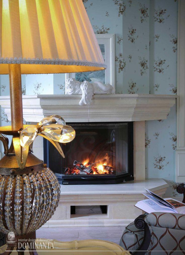 Интерьер гостиной с зоной камина оформлен в ностальгической стилистике американского дома. Портал камина выполнен из известняка, трапециевидный дымоход оклеен теми же синими в цветочек обоями, что и все стены в гостиной. На полу – дубовая доска под маслом.