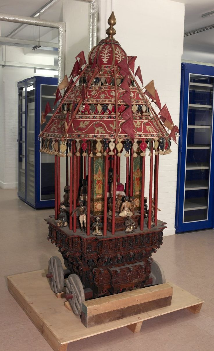 A model temple car or ratha. In wood (painted and unpainted), textile and metal. Adorned with Vishnu images painted on flat panels and many model attendant figures carved in the round. The whole is drawn by horses and attended by a small Garuda figure. T