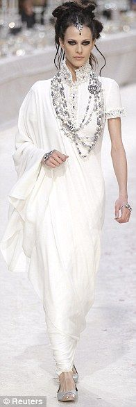 Sari-inspired long white dress with one loose draped side, exaggerated beaded stand collar, and layered necklaces.