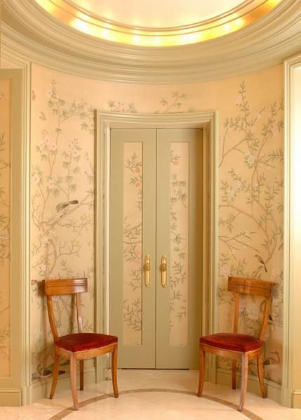 Blush pink chinoiserie on walls in a luxurious vestibule with ornate architectural round ceiling.