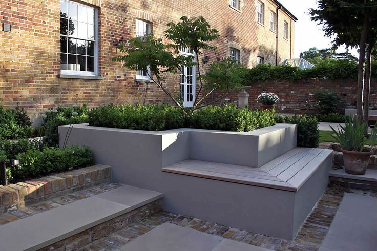 white rendered raised beds with integrated wooden seating and clipped greenery