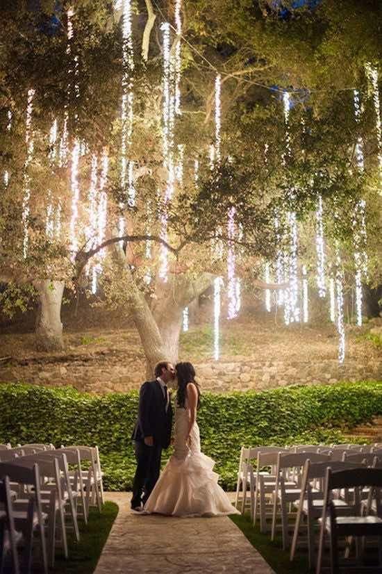 Decoración con luces de navidad colgantes: Luces colgantes de un árbol para una boda de noche al aire libre. Un backdrop impresionante para el beso tierno de los novios.