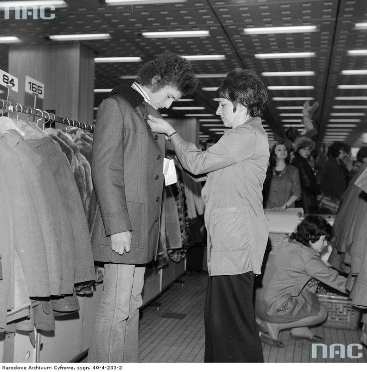 Stoisko z okryciami wierzchnimi. Ekspedientka pomaga klientowi przymierzyć kurtkę.