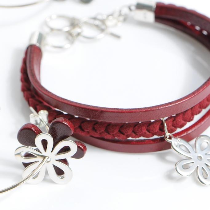 Set van leren armband met zilveren hangetje bloem motiefje, met bijpassende oorbellen.