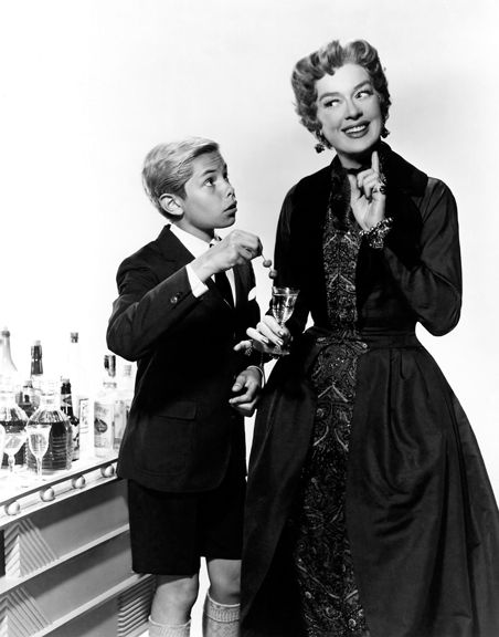 """""""Auntie Mame says olives take up too much room in such a little glass.""""  Rosalind Russell as Auntie Mame with Jan Handzlik as Patrick."""