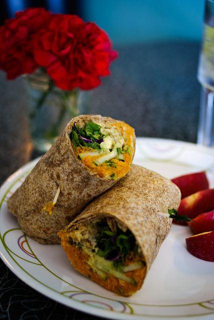 vegan hummus wrap with baked sweet potato, hummus, broccoli, cucumber, avocado, salad greens, tahini, and spicy walnuts