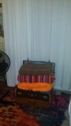 Blankets displayed and stored in vintage suitcases. Colorful crochet blanket handmade by my sister