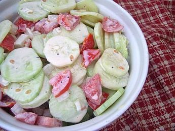 creamy cucumber and tomato salad::2 medium cucumbers, peeled and sliced   1 ripe tomato, cut into bite sized pieces   medium onion, diced   cup mayonnaise  1 tablespoon sugar  1 tablespoon milk  Salt and pepper to taste