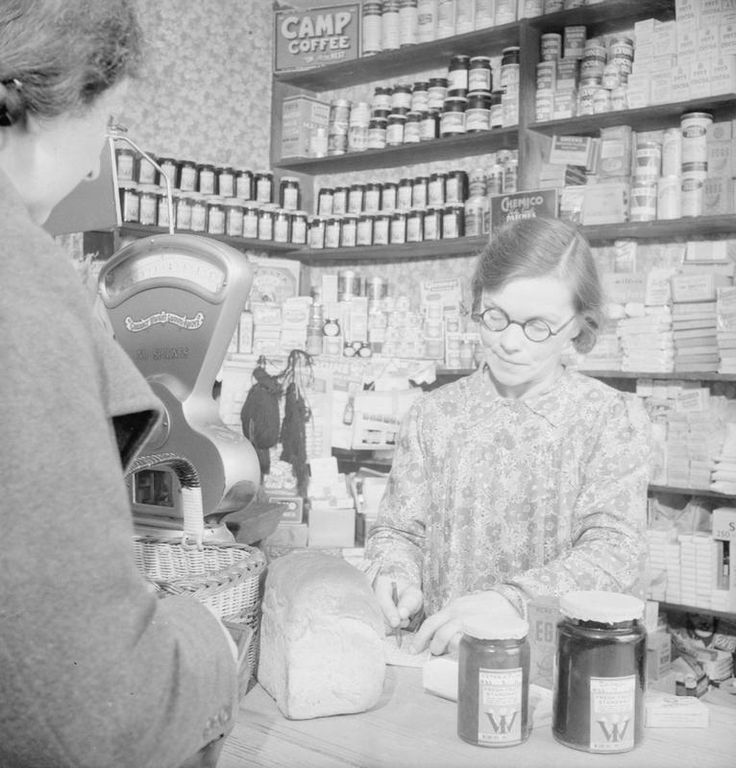 COMMUNITY GARDENING: WARTIME FOOD PRODUCTION AT ROWNEY GREEN, WORCESTERSHIRE, ENGLAND, UK, 1943 ~ Mrs Forsyth collects her jam ration from the shopkeeper in the village of Rowney Green in Worcestershire, as the shopkeeper checks off the coupons in Mrs Forsyth's ration book. The jam was made by women of the local Women's Institute in the village hall.