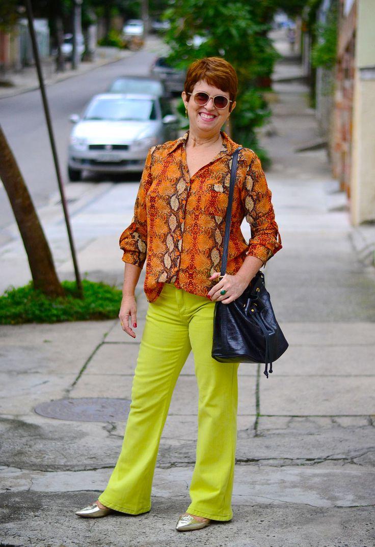 camisa com estampa de detalhes de couro de cobra em laranja e amarleo claro, calça flare verde limão, sapatilha bico fino dourada, bolsa saco preta