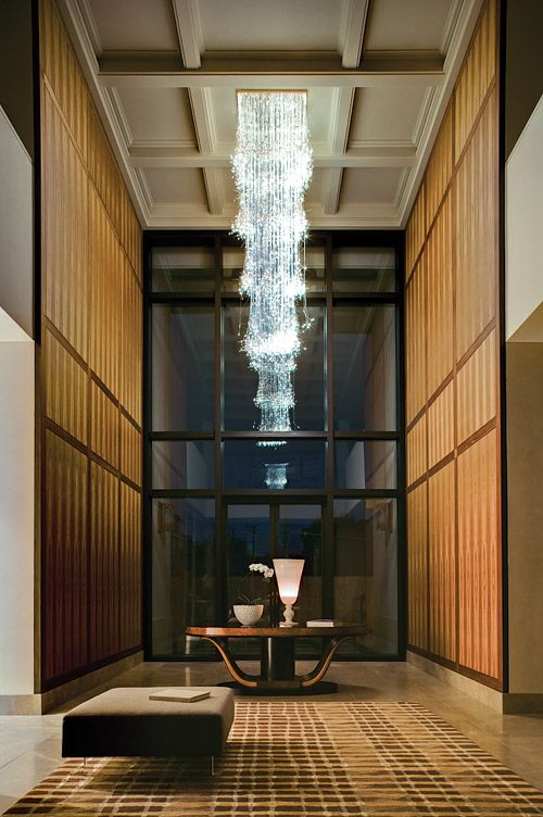 Entrance hall of a Melbourne residence by interior designer Thomas Hamel, featuring coffered ceiling and bronze inlaid black beam timber panelling. The commissioned cascade chandelier by Sharon Marston hangs above an Art Deco oval centre table.