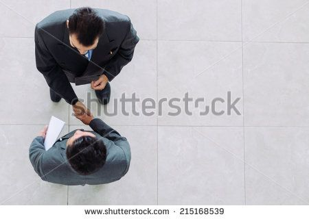 Business partners shaking hands as a symbol of unity, view from the top - stock photo
