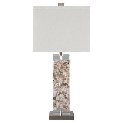 With its exquisite base, this shell table lamp radiates with an iridescent luster. Ultra-linear design brings a decidedly modern point of view to your space.  Signature Design by Ashley is a registered trademark of Ashley Furniture Industries, Inc.