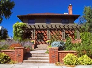 The upper story and pergola of this Foursquare take cues from the mossy green of the variegated brickwork. (Photo: John De Bord/Fotolia.com)