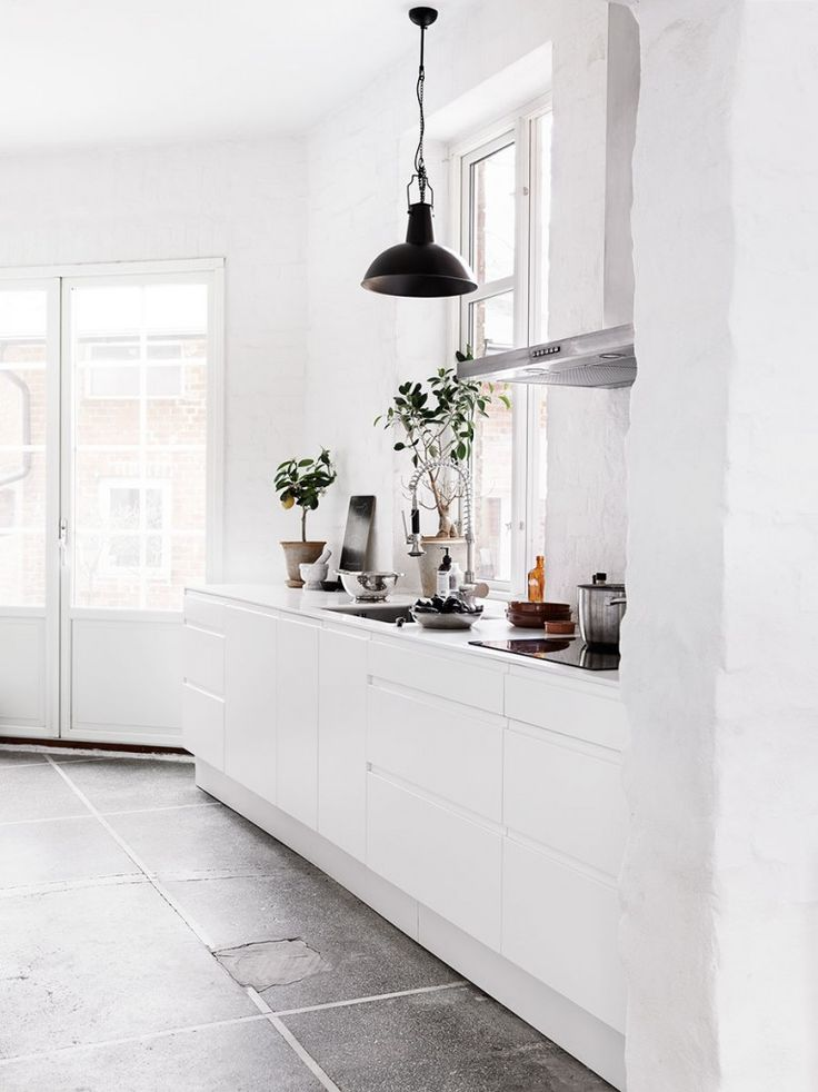 All white kitchen in an old industrial apartment