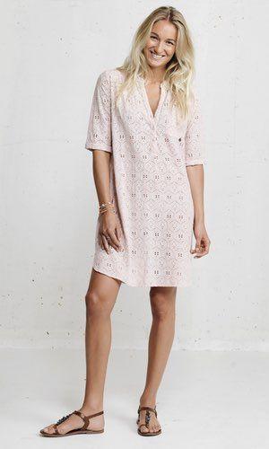 Araba Dress Feminin skjortekjole i broderie anglaise fra danske Plus Fine. Modellen har udskæring i V og lukkes med 3 knapper. Har halvlange ærmer og læg ved skulderpartil for og bag.  Materialet er 100% bomuld.