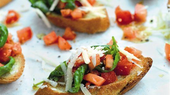 Lägg baguetteskivorna på en plåt med bakplåtspapper. Ringla över olivolja. Rosta i ugn på 225 grader ca 5 minuter. Blanda ihop tomater och vitlök och smaka av med olivolja, vinäger, salt och peppar. Vänd ner basilikan och lägg på brödskivorna, avsluta med att strö över rikligt med parmesanost.