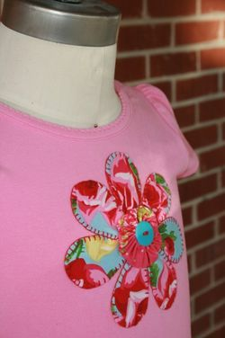 Cute applique idea with yo yo and button in center.  Could sew around petals with machine or blanket stitch...