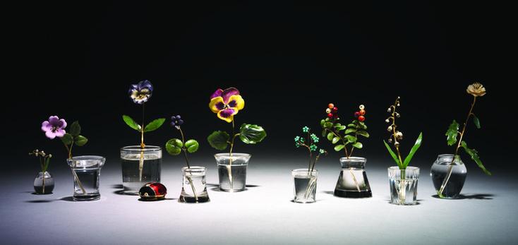 Еще одна область использования самоцветов в работе Фаберже - потрясающие воображение «каменные цветки», помещенные в «вазочки» из горного хрусталя, так искусно вырезанные, что в них будто бы налита вода. Стебельки изготовлены из золота и серебра, листики - из нефрита, лепестки окрашены эмалями и тщательно отполированы, так что цветок действительно кажется «живым».